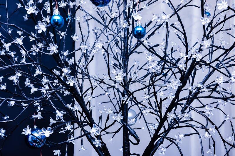 Depeszuje tkanego sztucznego drzewa z małymi kwiat lampami i obwieszeń błękitnych chrismass drzewnymi szklanymi piłkami obrazy stock