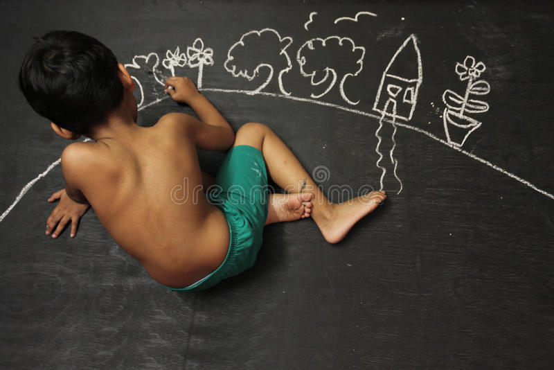 Depicting Dream. I cute Indian baby boy depicting his dream for sweet home, It drawing home with Chalk on blackboard royalty free stock images
