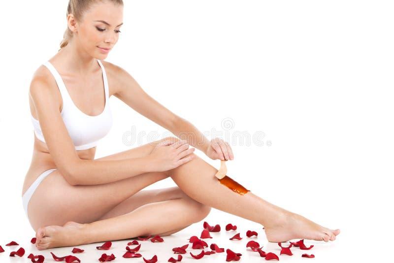 Depilación de piernas femeninas con encerar en el fondo blanco imagen de archivo libre de regalías