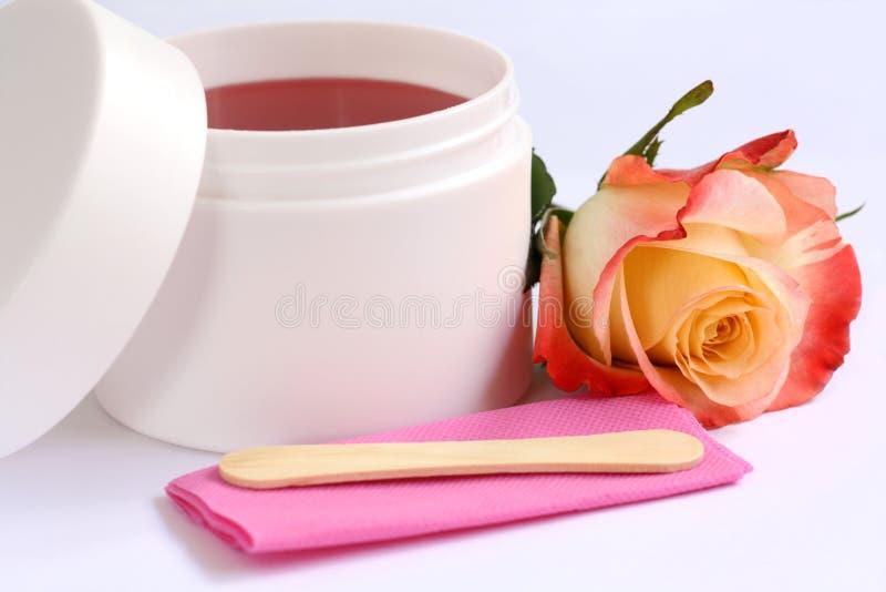 Depilación fijada: el envase de la cera, palillo y subió imagen de archivo libre de regalías