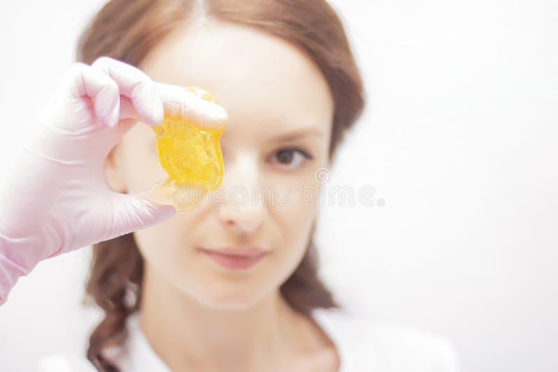 Depilation ζάχαρης η καλλυντική διαδικασία που ο όμορφος κύριος κοριτσιών κρατά την κόλλα ζάχαρης στα χέρια στοκ φωτογραφία