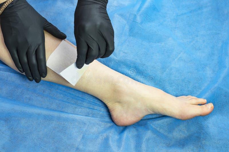Depilation τα θηλυκά πόδια και παραδίδουν ένα σαλόνι ομορφιάς στοκ εικόνες