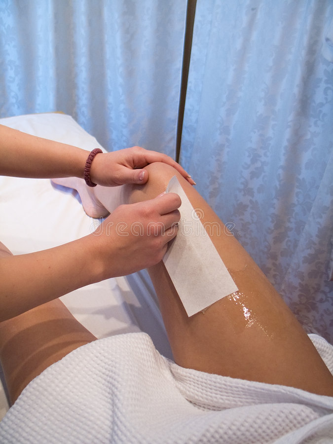 Depilation. Tights depilation with wax in beauty salon royalty free stock image