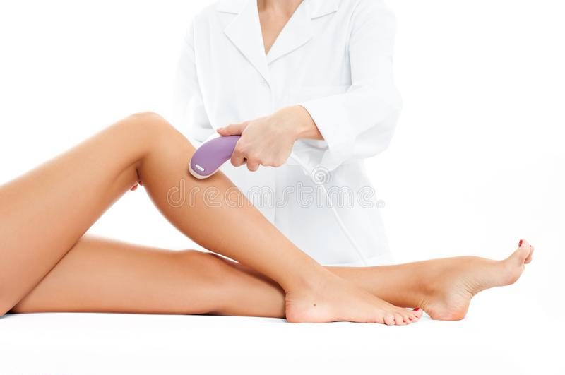 Beautician removing hair of woman`s leg. Laser epilation royalty free stock images