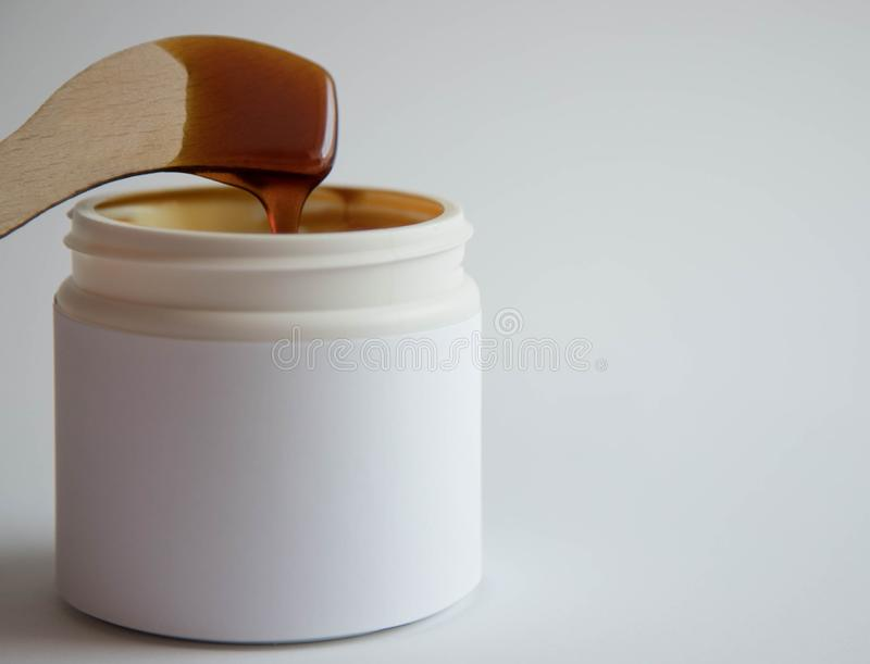 Depilation and beauty concept - sugar paste or wax for hair removal in a white plastic jar with a wooden wax spatula in molten royalty free stock image