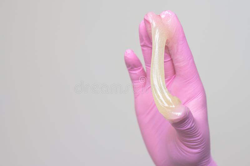 sugar paste or wax honey for hair removing with pink gloves hands of cosmetologist in spa salon - depilation and beauty concept stock images