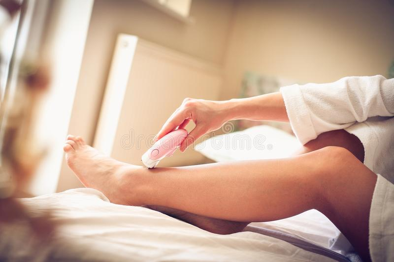 Depilation legs on bed. Morning is for body care. stock photos