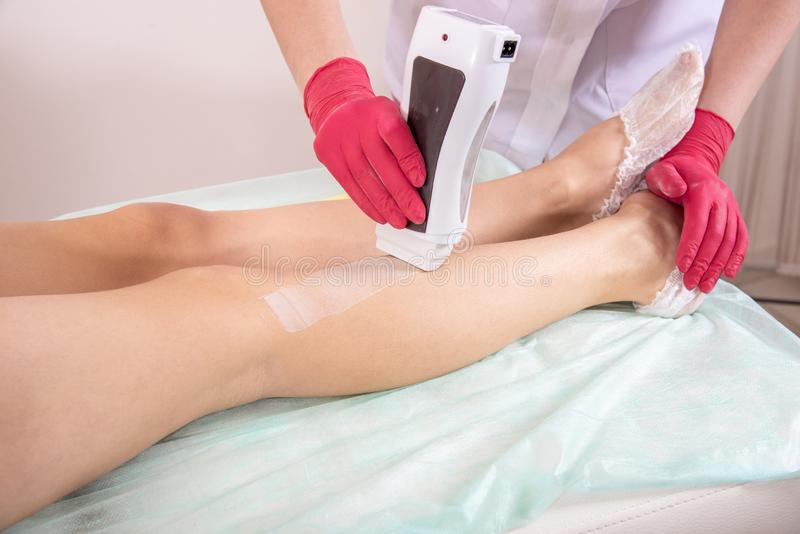 Depilation master in gloves applies melted wax to female legs. Depilation master in red gloves applies melted wax to female legs royalty free stock photography
