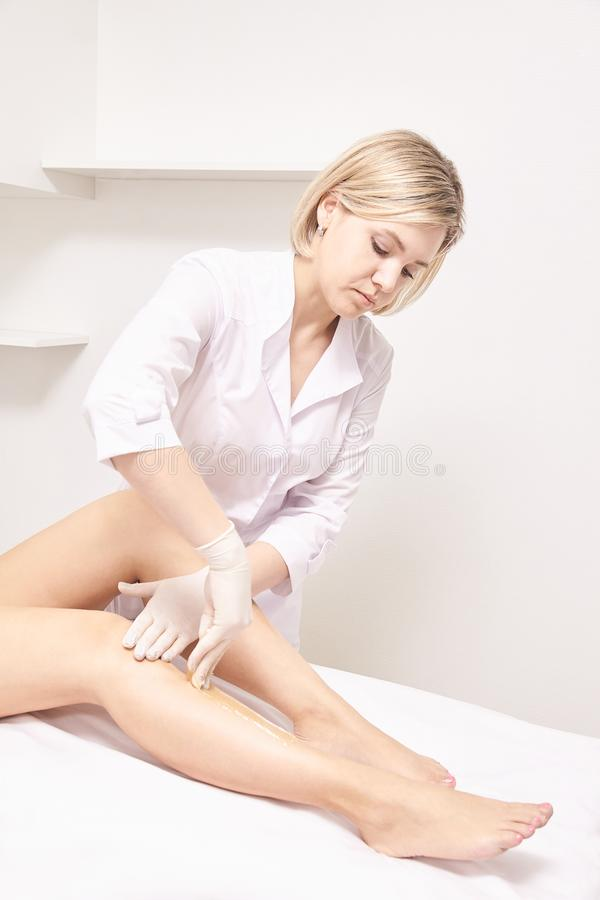 Depilation spa procedure. Woman hair remove waxing. Epilation sugaring. Legs foot stock photography