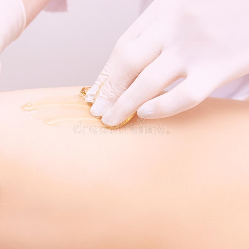 Depilation spa procedure. Woman hair remove waxing. Epilation sugaring. Legs foot stock photo