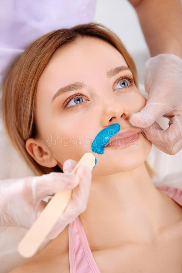 Depilatory master removing unwanted hair under nose of client. Unwanted hair. Experienced professional depilatory master removing unwanted hair under nose of her stock images