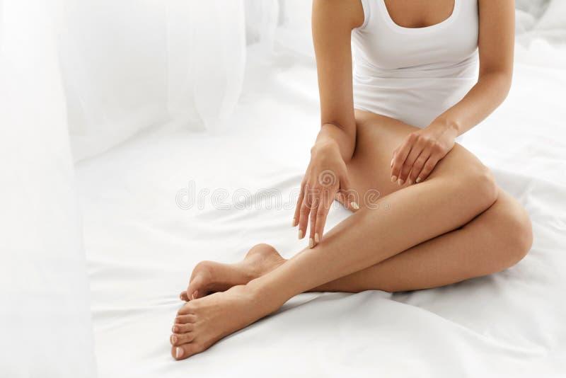 Depilazione Chiuda sulle mani della donna che toccano le gambe lunghe, pelle molle fotografie stock libere da diritti