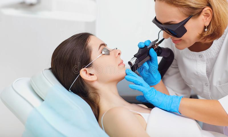Depilazione del laser sul fronte di una giovane donna in una cosmetologia fotografia stock libera da diritti