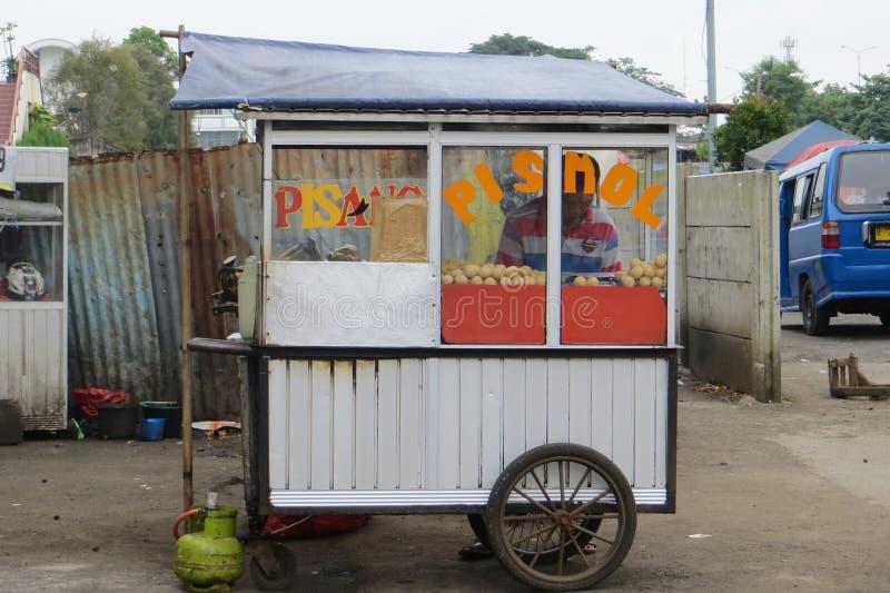 Street food vendor in Depok. DEPOK, INDONESIA - March 10, 2017: Street vendor selling pismol pisang molen or fried banana on Jalan Margonda royalty free stock photos