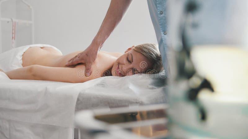 Deponuje pieniądze z medycznymi pijawkami przeciw masażowi dla blondynki dziewczyny zdjęcie royalty free