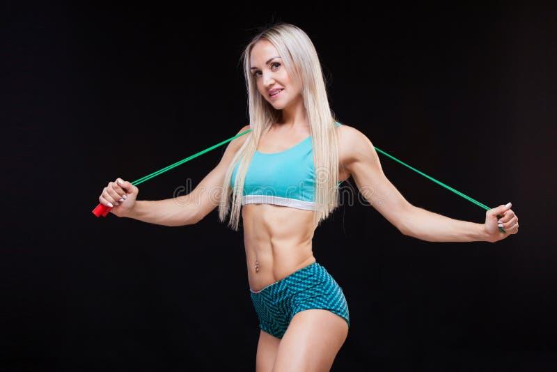 Deporte, actividad Mujer linda con la cuerda que salta Fondo muscular del negro de la mujer fotografía de archivo libre de regalías