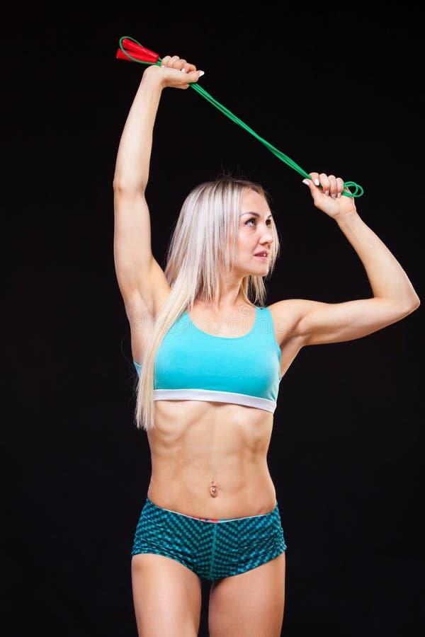 Deporte, actividad Mujer linda con la cuerda que salta Fondo muscular del negro de la mujer imagenes de archivo