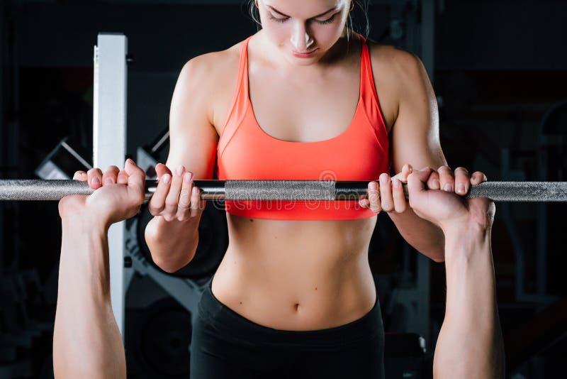 Deporte, aptitud, trabajo en equipo, levantamiento de pesas y concepto de la gente - trabajo personal del instructor de la chica  imagenes de archivo