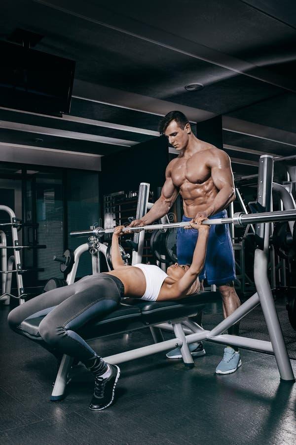 Deporte, aptitud, trabajo en equipo, levantamiento de pesas y concepto de la gente - mujer joven e instructor personal con doblar foto de archivo