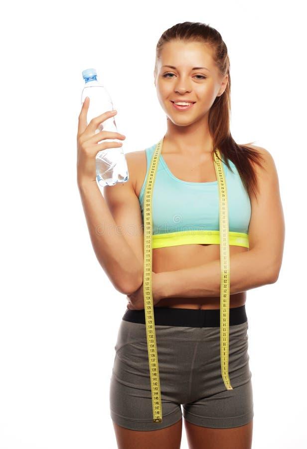 Deporte, aptitud y concepto de la gente: Mujer sonriente feliz joven en ropa de deportes con agua, fotos de archivo