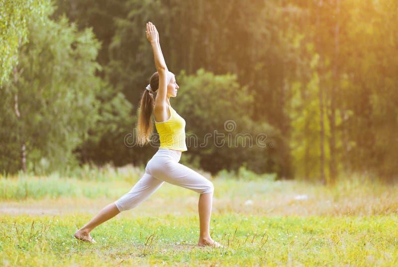 Deporte, aptitud, yoga - concepto, mujer que hace ejercicio al aire libre imagen de archivo libre de regalías
