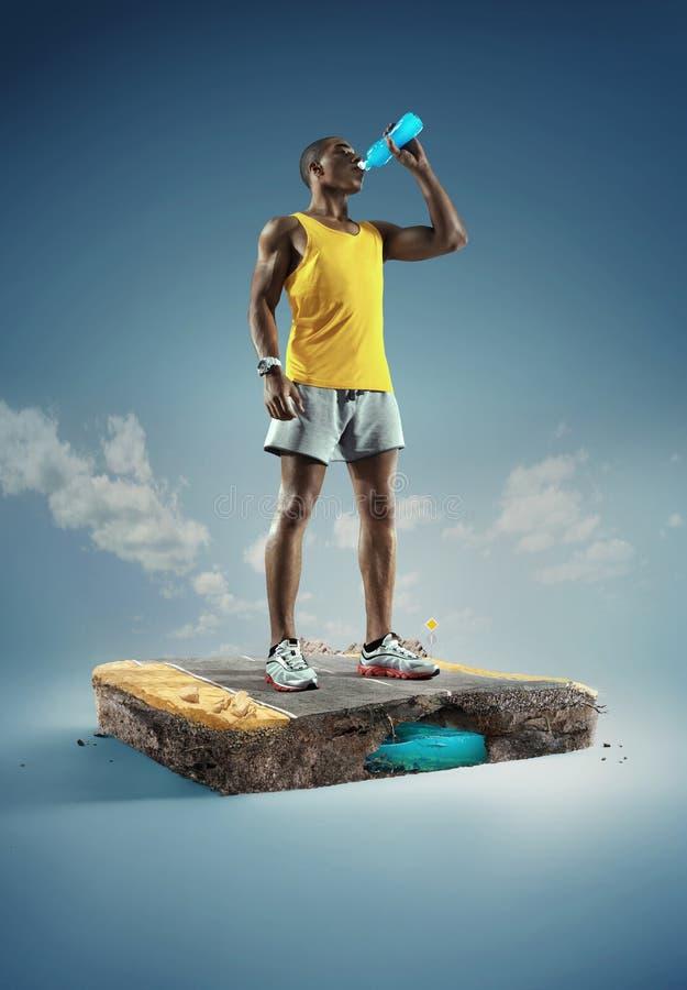 Deporte corredor Agua potable del hombre muscular joven de la estructura de la botella después de correr foto de archivo libre de regalías