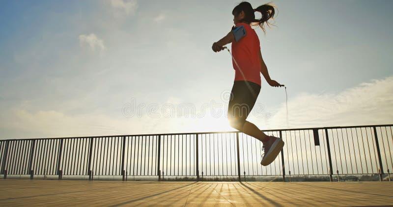 Deporte de la mujer y el saltar de la cuerda foto de archivo libre de regalías
