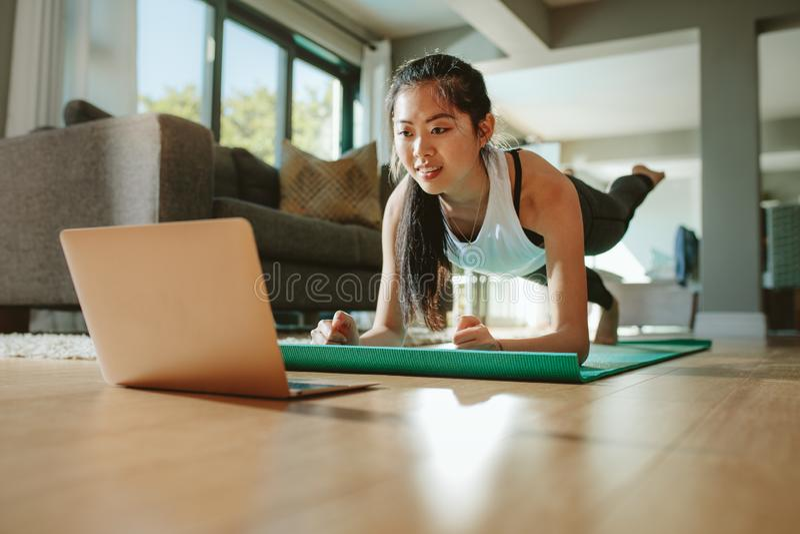 Deporte de observación de la mujer que entrena en línea en la tableta imágenes de archivo libres de regalías