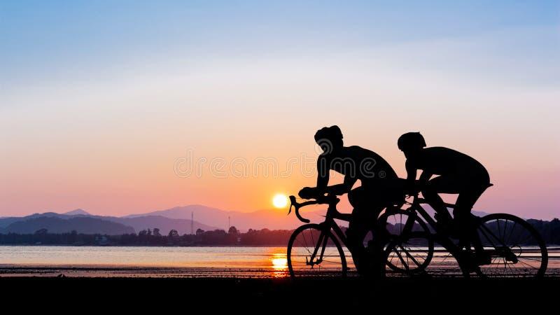 Deporte del Triathlon en la playa el tiempo de la puesta del sol foto de archivo libre de regalías