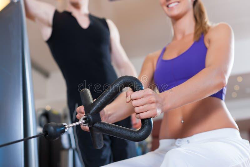Deporte - el par está ejercitando en las máquinas en gimnasia fotografía de archivo libre de regalías