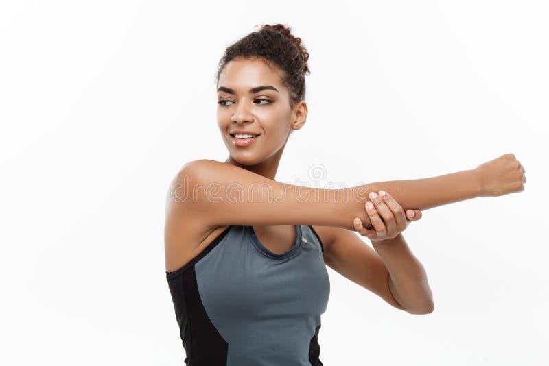 Deporte, entrenamiento, forma de vida y concepto de la aptitud - retrato de la mujer afroamericana feliz hermosa que estira las m imagen de archivo