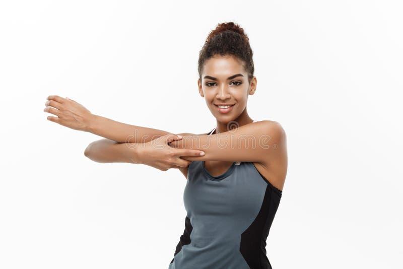 Deporte, entrenamiento, forma de vida y concepto de la aptitud - retrato de la mujer afroamericana feliz hermosa que estira las m fotos de archivo