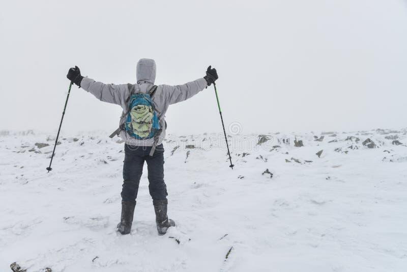 Deporte extremo Caminante solitario en las montañas del invierno que se colocan en el top con para arriba aumentados los hads fotografía de archivo