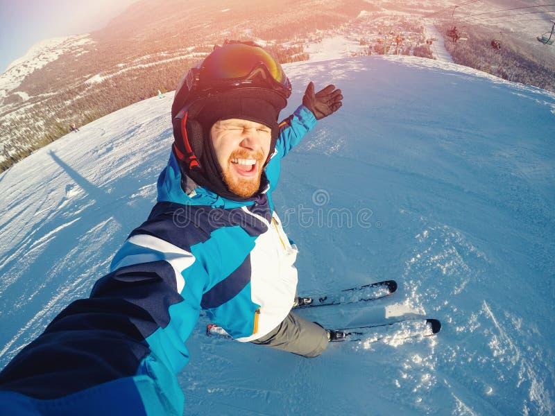 Deporte extremo del invierno con la cámara de la acción del selfie Paseos del hombre en los esquís de las cuestas en casco protec imagenes de archivo