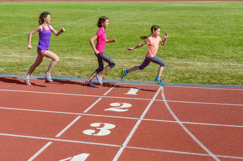 Deporte, madre y niños de la familia corriendo en pista del estadio, el entrenamiento y la aptitud de los niños imágenes de archivo libres de regalías