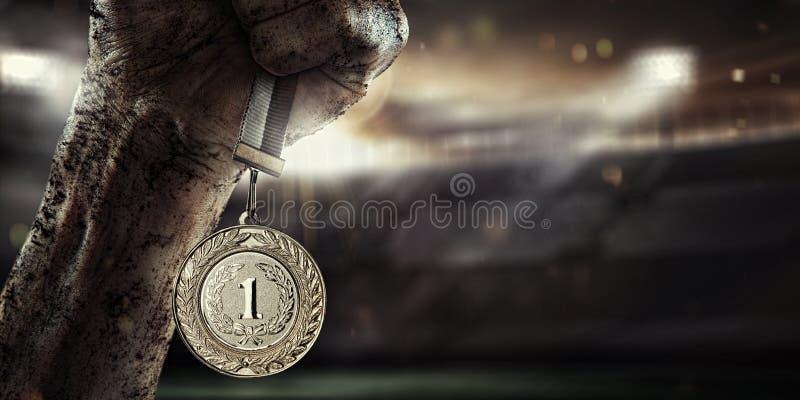 Deporte, mano masculina que sostiene la medalla de oro fotos de archivo libres de regalías