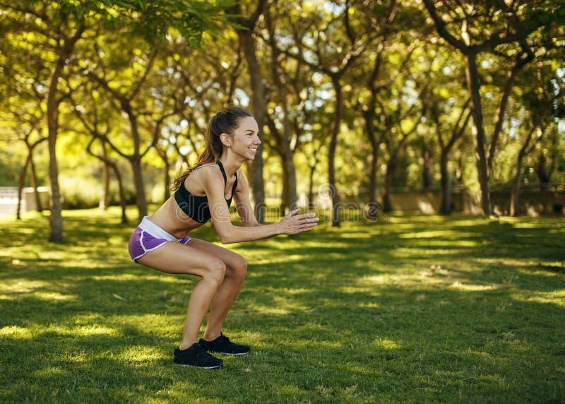 Deporte practicante de la muchacha que hace posición en cuclillas en el parque fotos de archivo libres de regalías