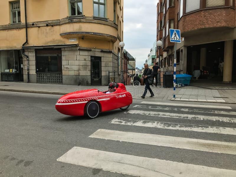 Deporte rojo moderno del mango de Velomobile con el conductor imagenes de archivo