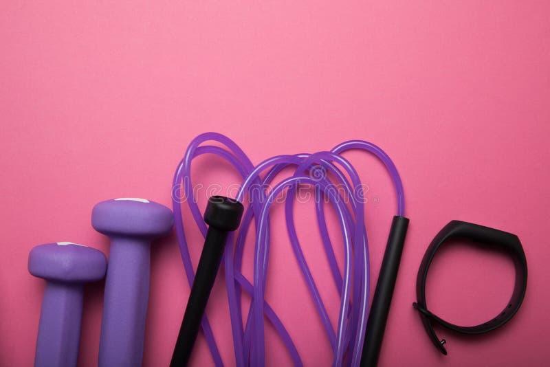 Deporte y atletismo, pesa de gimnasia y cuerda que salta con una pulsera de la aptitud en un fondo rosado imágenes de archivo libres de regalías