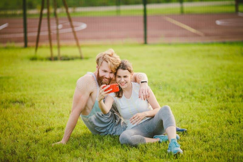 Deporte y tecnología Jóvenes en los pares caucásicos heterosexuales del amor que descansan después de entrenamiento al aire libre fotografía de archivo libre de regalías