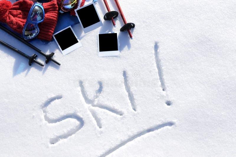 Deportes de invierno de las vacaciones del esquí concepto, palabra escrita en nieve con el equipo del esquí e impresiones polaroi fotos de archivo libres de regalías