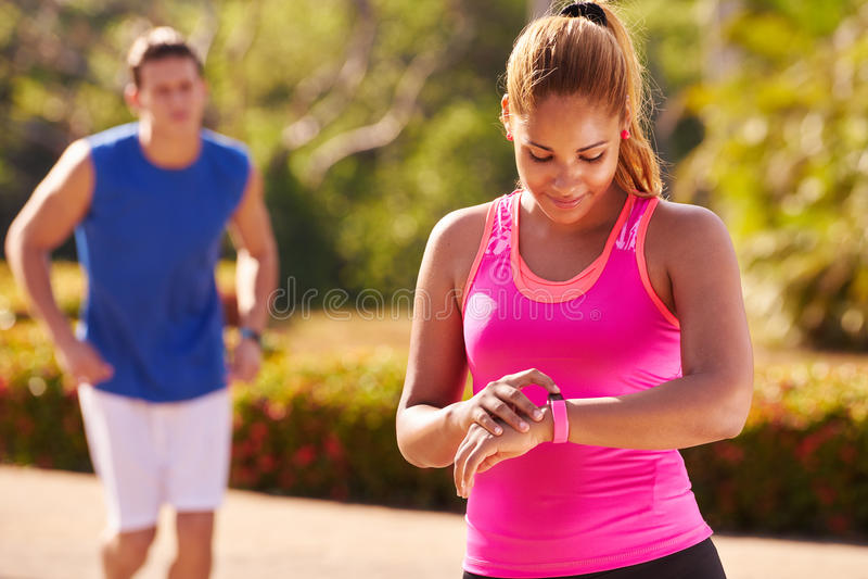 Deportes de la mujer joven que entrenan al contador de pasos de Fitwatch de la aptitud imagen de archivo libre de regalías