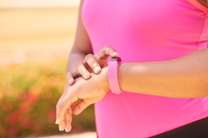 Deportes de la mujer que entrenan usando contador de pasos de Fitwatch de la aptitud fotos de archivo