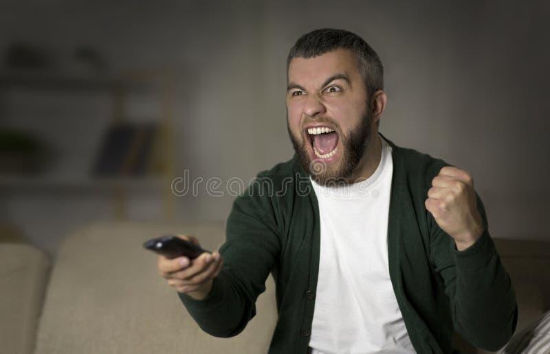 Deportes de observación del hombre barbudo emocional en la TV en casa imagenes de archivo