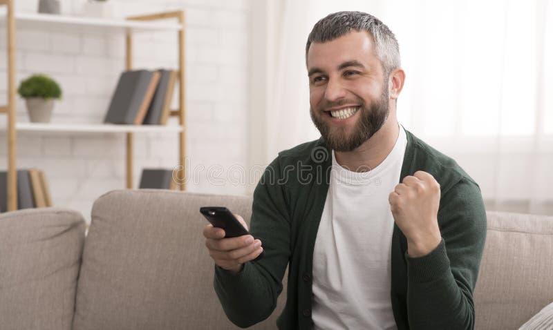 Deportes de observación del hombre barbudo feliz en la TV en casa imagen de archivo