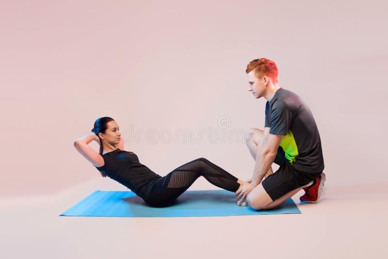 Deportes muchacha e individuo que hacen ejercicios Él ayuda a la muchacha a oscilar la prensa En un fondo ligero, un lugar para e fotos de archivo libres de regalías