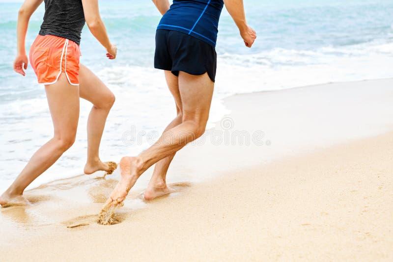 deportes Piernas atléticas de los corredores que corren en la playa entrenamiento Sano fotografía de archivo libre de regalías