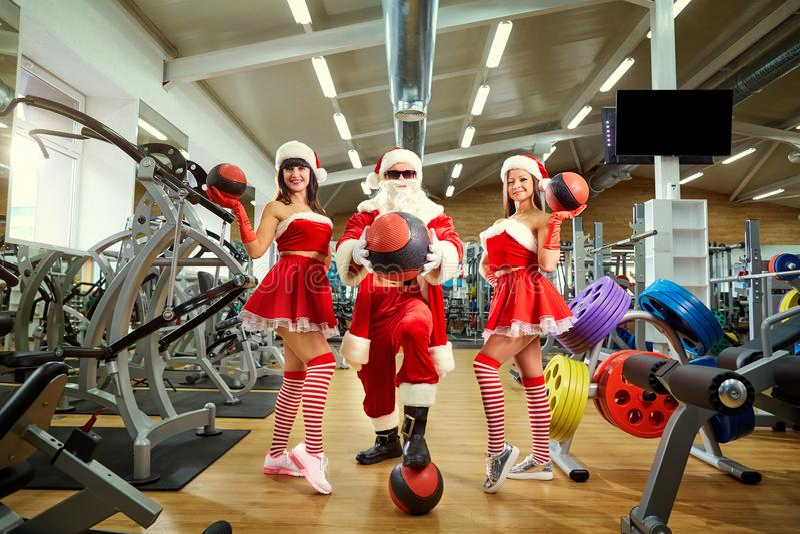 Deportes Santa Claus con las muchachas en trajes del ` s de Papá Noel en el gimnasio encendido fotografía de archivo libre de regalías