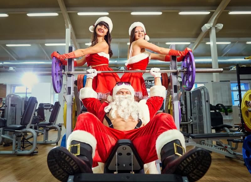 Deportes Santa Claus con las muchachas en trajes del ` s de Papá Noel en el gimnasio encendido imagenes de archivo