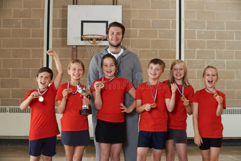Deportes victoriosos Team With Medals And Trophy de la escuela en gimnasio imagenes de archivo